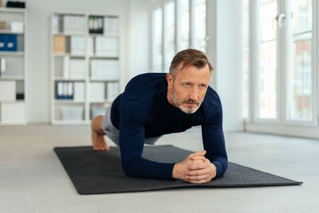 Athletic man doing plank exercises in a gym in a low angle view at floor level
