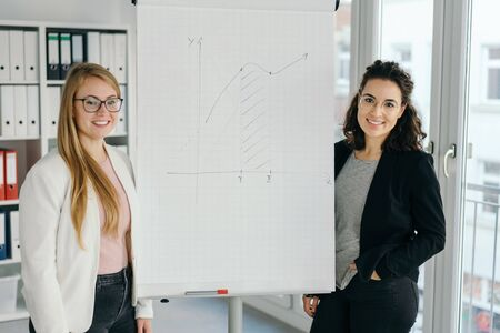 Confident young business partners or team colleagues giving a presentation standing flanking a flip chart with infographic smiling at the camera