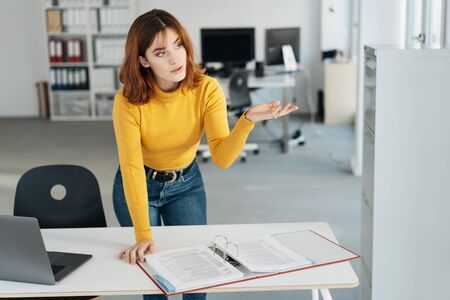 Young businesswoman gesturing with her hand as she converses with someone off frame while leaning over a large office binder of paperwork Banque d'images