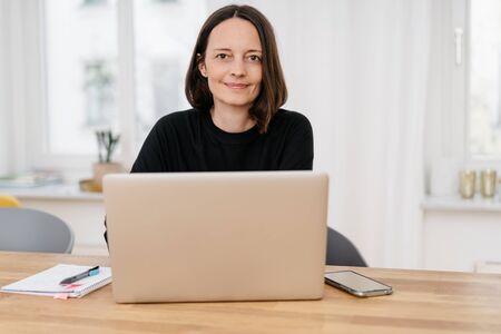 Friendly woman sitting working on a laptop in a home office looking over the top smiling at the camera
