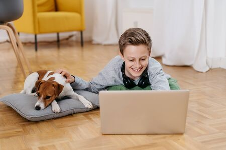 Smiling little boy relaxing at home with his dog as they lie together on the parquet floor in the living room working on a laptop computer
