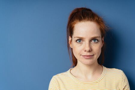 Pretty young redhead woman with large blue eyes smiling quietly at the camera in a close up portrait on a blue studio background with copy space Stock Photo