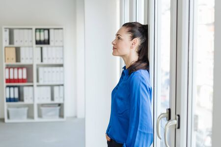 Young brunette woman in blue shirt leaning back on bright office windows, viewed from her side with copy space