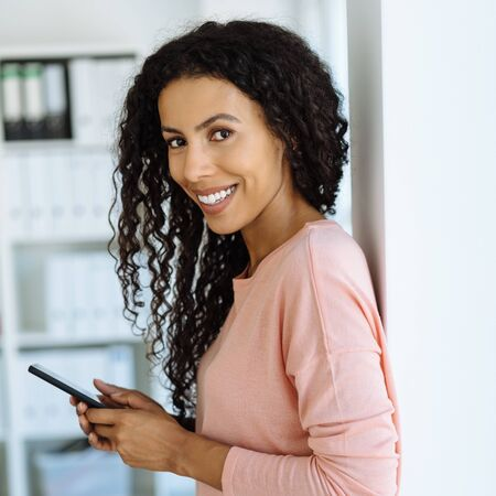 Smiling friendly young African woman with long curly hair leaning against an interior wall holding a mobile phone turning to look at the camera