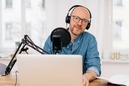 Man wearing earphones looking quizzically at the camera around the side of a professional microphone as he works on a recording a podcast on his laptop