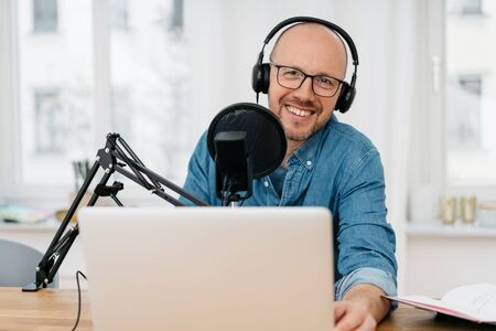 Happy friendly man recording a podcast on a laptop computer with earphones and microphone as he looks at the camera with a beaming smile