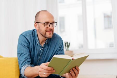 Middle-aged man wearing reading glasses sitting in a chair in his high key living room reading a book with a quiet smile of pleasure