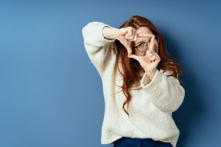 Creative young woman making a frame gesture with her hands as she visualises her latest project on a blue studio background with copy space Фото со стока
