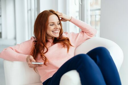 Young woman smiling happily as she watches through a window while relaxing in a comfortable chair with her mobile phone Reklamní fotografie