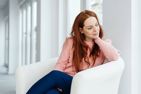 Young redhead woman relaxing in a comfy chair turning to gaze out of a window behind her in a bright high key interior Reklamní fotografie