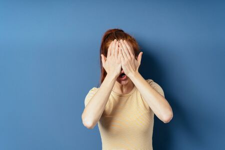Young slender redhead woman covering her face with her hands as she speaks to the camera on a blue studio background with copy space