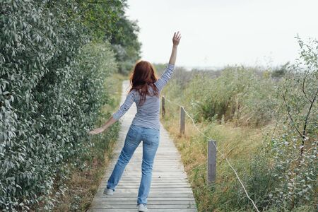 Carefree young woman dancing along a boardwalk with hands waving in a rear view on coastal dunes 写真素材