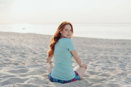 Young woman sitting on a beach looking back over her shoulder with a quizzical expression at the camera