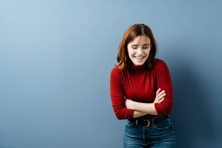 Natural young woman laughing in amusement bending forwards with a vivacious smile and folded arms over a blue studio background with copy space