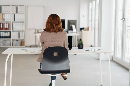 Rear view of a young businesswoman working at a desk in a high key spacious modern office with copy space