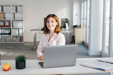 Smiling young friendly businesswoman at her desk seated behind a laptop computer in a high key modern office