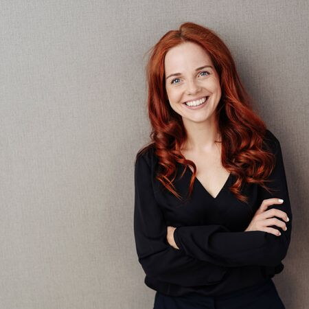 Young and beautiful smiling red-haired woman in black v-neck shirt, standing with arms folded against grey wall. Half-length front portrait with copy space Foto de archivo