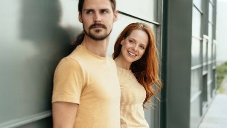 Pretty redhead woman peering around her boyfriend with a smile as they stand together against a grey exterior wall looking to the side watching