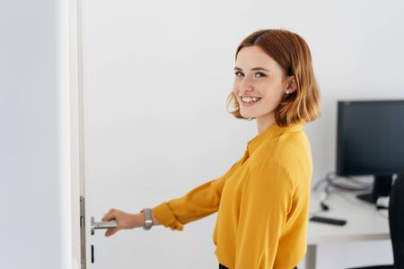 Smiling young businesswoman leaving the office turning back to say goodbye with her hand on the handle of the door Stock Photo