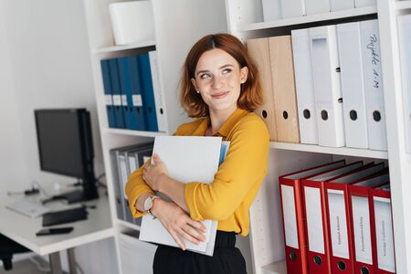 Happy young businesswoman standing daydreaming clutching a large office binder to her chest as she looks up with a smile of pleasure Banque d'images