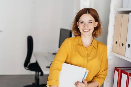 Relaxed friendly young businesswoman holding a binder under her arm leaning against shelves in the office smiling at the camera
