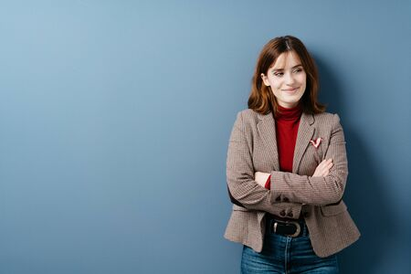 Relaxed young woman in smart jacket and jeans standing looking aside with amusement smiling happily to herself with folded arms over a blue studio background with copy space