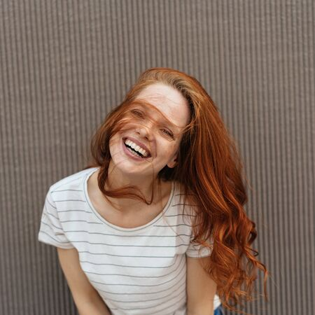 Happy young woman laughing happily as she leans towards the camera with her hair blowing across her face in square format over a textured wall background