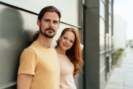 Handsome bearded young man with ponytail standing against a wall in an urban street with a woman friend turning to look thoughtfully at the camera