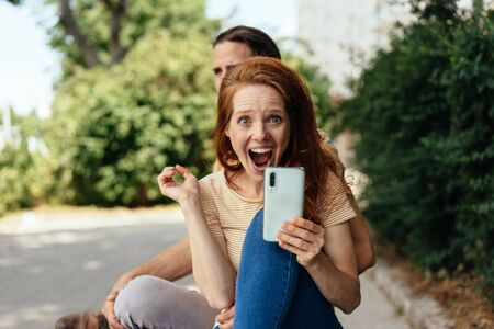 Excited young woman holding her mobile phone gawping wide eyed at the camera in sock and surprise outdoors on a quiet street in town Zdjęcie Seryjne