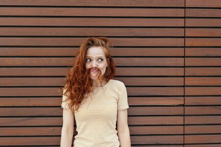 Fun loving young woman making a spoof mustache with a strand of her long red hair over her upper lip looking aside with a mischievous expression