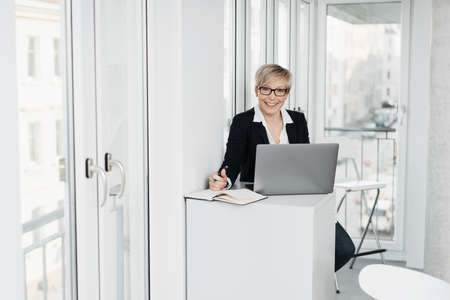 Happy friendly businesswoman or receptionist seated working at a laptop taking notes looking up at the camera with a smile in a high key office Standard-Bild
