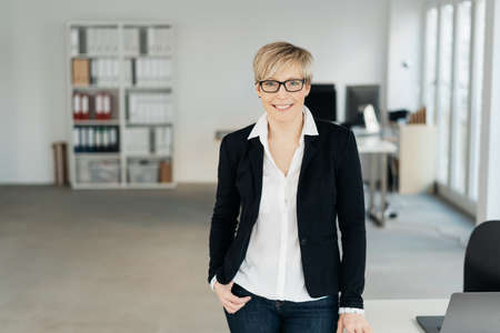 Relaxed smart businesswoman in spacious office standing smiling at the camera alongside her desk with lateral copy space