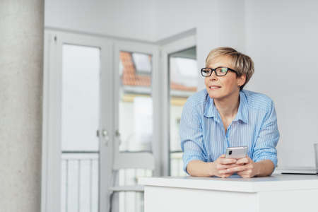 Woman standing leaning on a white wooden cabinet watching with a look of fascination while holding her mobile phone indoors in a high key room with copy space 写真素材