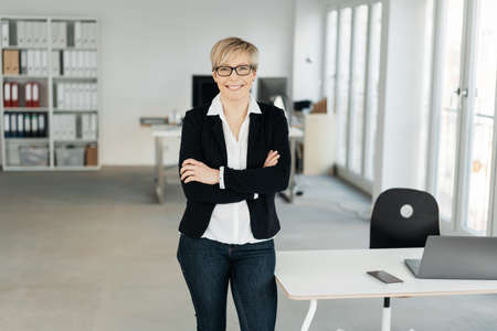 Confident happy smart businesswoman standing with folded arms in a high key spacious office smiling at the camera, with copy space Standard-Bild