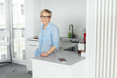 Happy relaxed woman standing in her kitchenette in a high key apartment smiling happily at the camera