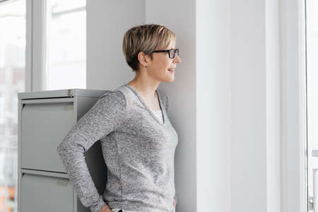Female office worker wearing glasses standing watching through a window with a quiet smile in a profile view