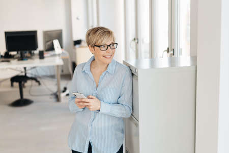 Happy relaxed businesswoman watching out of a window with a smile as she stands leaning on an office cabinet with her mobile phone in her hands