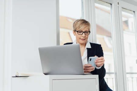 Businesswoman checking her mobile phone as she sits at an office cabinet behind a laptop computer in a low angle view in a high key office
