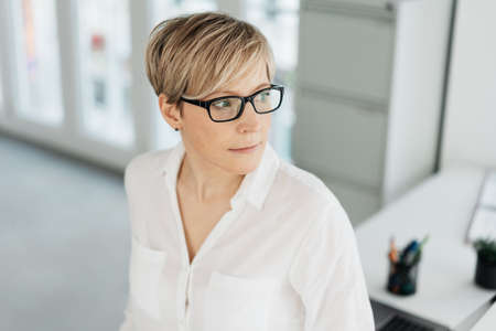 Thoughtful woman wearing spectacles standing watching to the side in a close up portrait indoors with a pensive serious expression