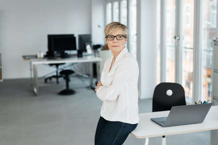 Businesswoman looking aside with pensive expression watching over her shoulder through a window as she perches on the edge of her desk with copy space Standard-Bild