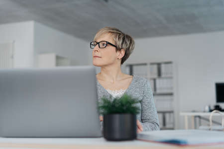 Businesswoman seated at a desk watching to the side with a thoughtful expression in a low angle view Standard-Bild