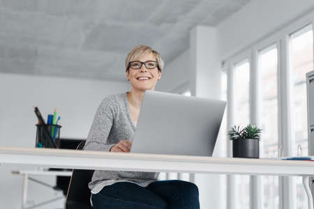 Low angle view of a businesswoman sitting working at a laptop computer in a high key office as she looks up with a smile watching something