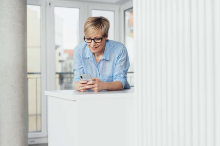 Housewife relaxing at home using her mobile phone leaning on a white cabinet texting with a smile with copy space alongside Standard-Bild