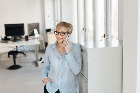 Businesswoman standing chatting on a mobile phone as she relaxes leaning against an office cabinet with a smile Standard-Bild