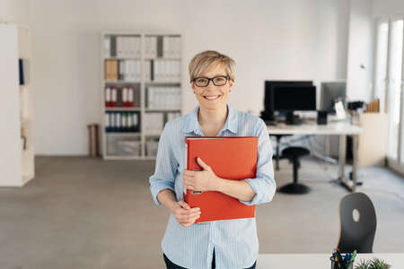 Smiling happy businesswoman clutching a large red binder to her chest as she stands in a spacious modern office