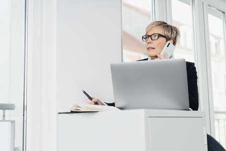 Businesswoman listening to a mobile phone call in a low angle view as she sits at her desk in the office working on a laptop computer