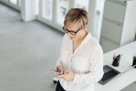 Businesswoman standing texting a mobile message as she perches on the end of an office table in a high key portrait from a high angle with copy space