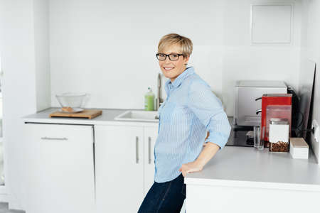 Smiling friendly housewife standing in a kitchen leaning against the counter turning to look at the camera
