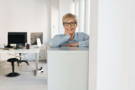 Smiling businesswoman wearing glasses standing leaning on a cabinet in the office looking at the camera with copy space