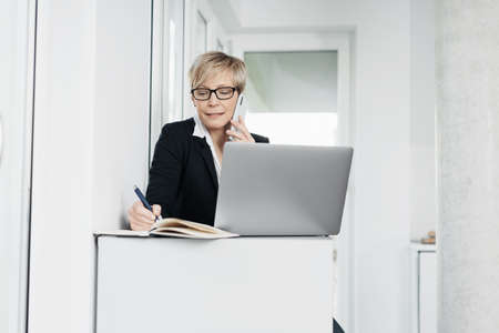 Businesswoman or receptionist talking on a mobile phone in the office as she takes notes in a journal alongside her laptop computer Standard-Bild